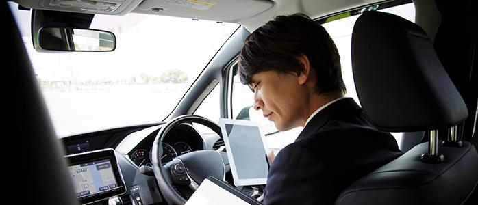 車内でタブレットと運転指示書を確認するドライバー