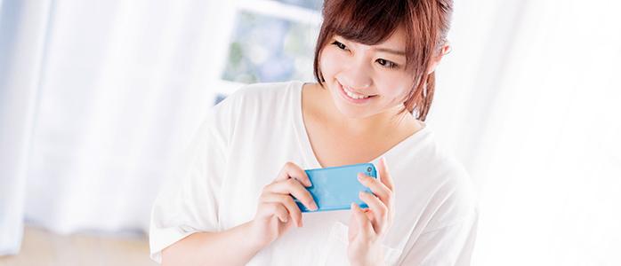 スマホを手に取り笑顔を見せる若い女性