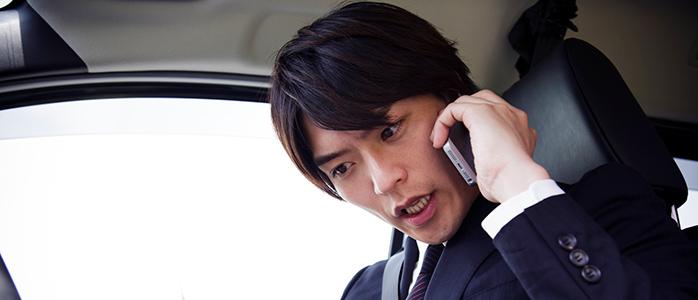 顧客の電話に真摯に対応する運転手