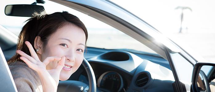 OKサインを作り笑顔を見せる運転席の女性