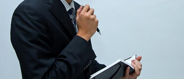 手帳にスケジュールを書き込む男性